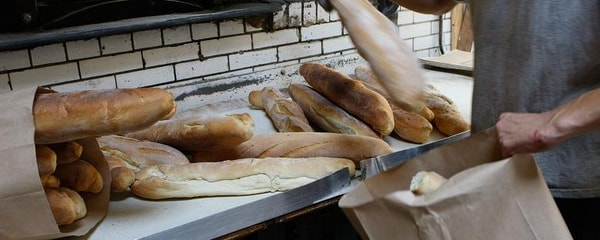 Cropped view of freshly baked bread in a bakery being placed into paper bags in San Francisco.