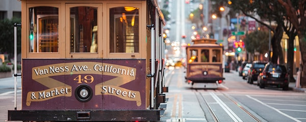 View of two trolleys running on San Francisco tracks.