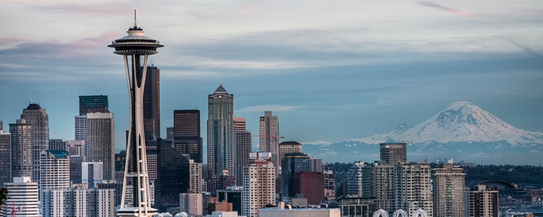 Skyline view of the Seattle Space Needle with Mount Rainer in the background.