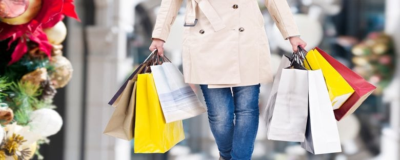 A satisfied shopper walks among the shops of Toronto, Canada with bags full
