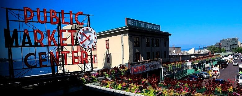 Full view of signage for the Pike Place Market in Seattle under blue sky.