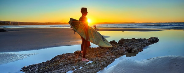 A surfer holding his surfboard on a beach in Gold Coast, Australia as the sun is setting.