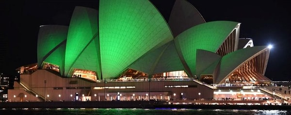 The iconic sails of the Sydney Opera House are lit bright green at night