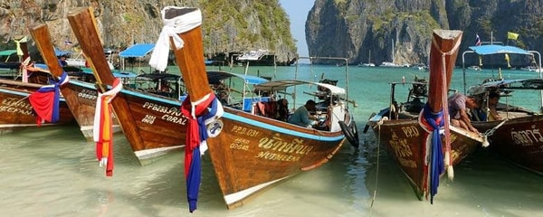 Up close view of fishing boats resting on the beach in shallow waters in Thailand.