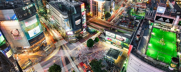Birds eye view over the Shibuya Scramble Crossing at night with bright lights and racing cars.