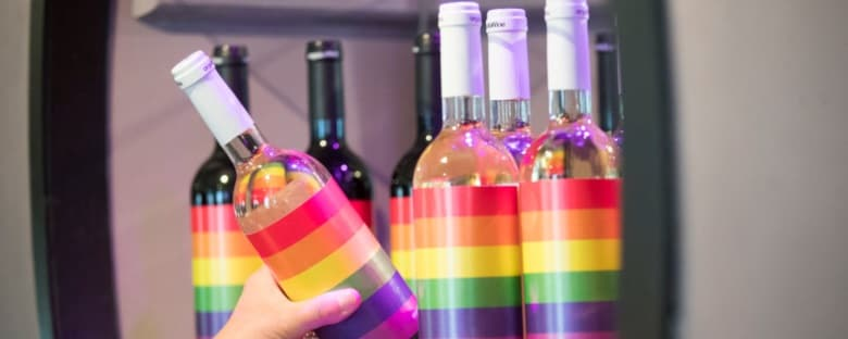 Wine bottles decorated like rainbows being taken off a shelf in Toronto.