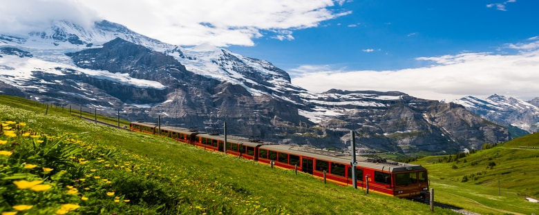 A train traveling through Europe near green hills and snow-capped mountains.