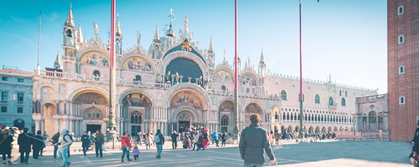A tourist walking through St. Mark's Square in Venice, Italy.