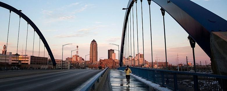 A woman running on a bridge towards the Des Moines skyline.