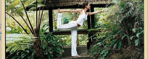 Full view of a woman doing a yoga pose in the lush mountains of Bali, Thailand.