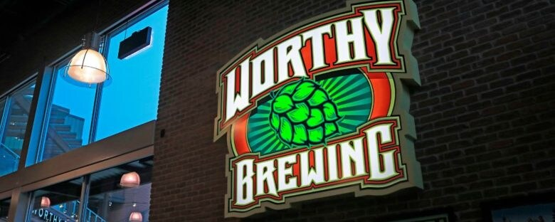 Low angle view of a Worthy Brewing sign hung on a brick wall in Bend Oregon.