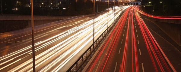Long-exposure shot captures the lights of cars streaking down the Autobahn near Berlin at night