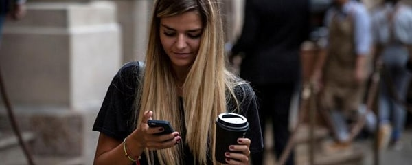 A young woman checks her phone after getting coffee in a local café in Calgary