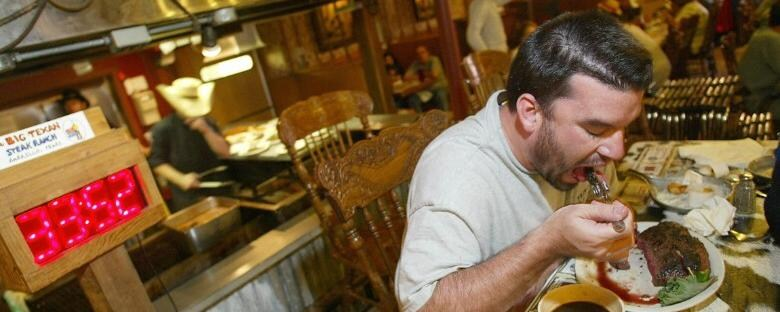 Man enjoys a meal at a steak house restaurant in Cleveland, Ohio