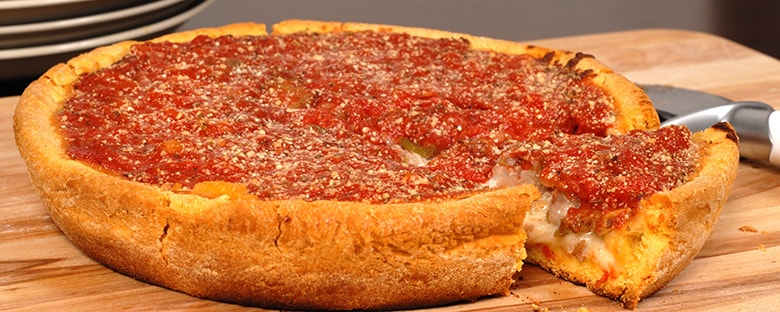 View of a large Chicago style deep dish pizza with a piece cut out.