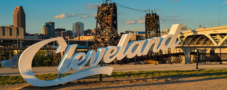 View of the Cleveland sign under a shadow with the city in the background under a blue sky.