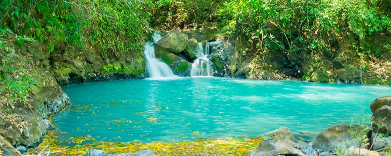 Turquoise waters and a waterfall surrounded by green trees in Costa Rica.