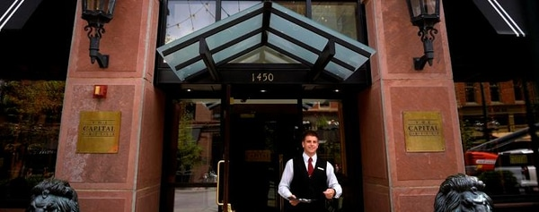 A waiter exits a restaurant in downtown Denver to greet patrons dining outside