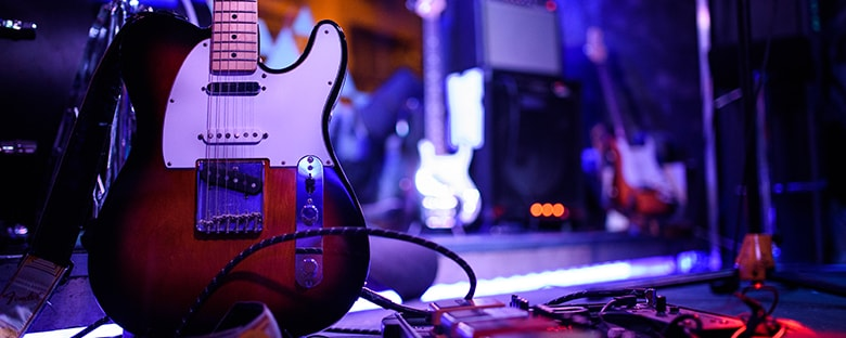 Close up view of an electric guitar sitting on stage next to a drum set under a blue light.