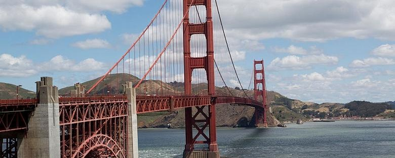 Full view of the Golden Gate Bridge under a partly cloudy sky with hills in the background.