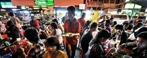 A crowd packs street food stalls in Jakarta, Indonesia for the evening meal
