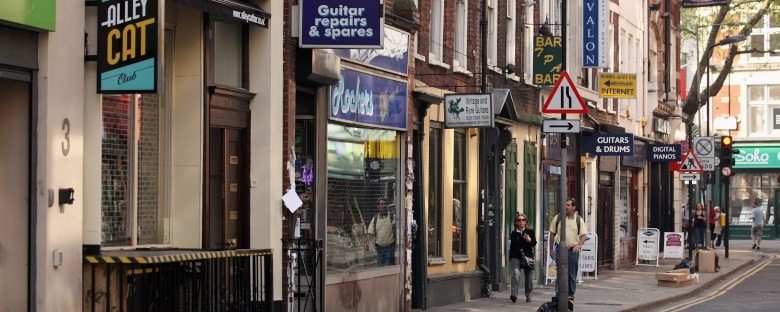 Signs mark the entrances to independent shops in Soho neighbourhood of London