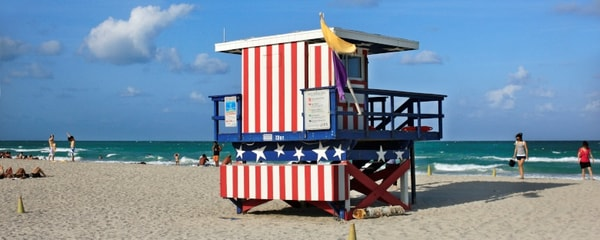 A lifeguard stand on the beach under a blue sky on a summer day.