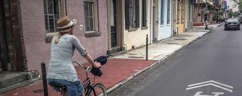 View of a bike rider riding through the French Quarter next to buildings in New Orleans.