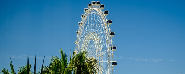 A Ferris wheel spinning on a sunny day in Orlando, Florida.