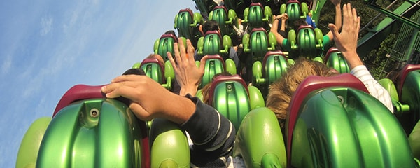 View of bright green roller coaster seats in motion with excited hands up in the air in Orlando.