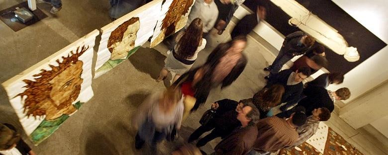 Birds eye view inside of a Phoenix art gallery looking at guests viewing pieces of art.