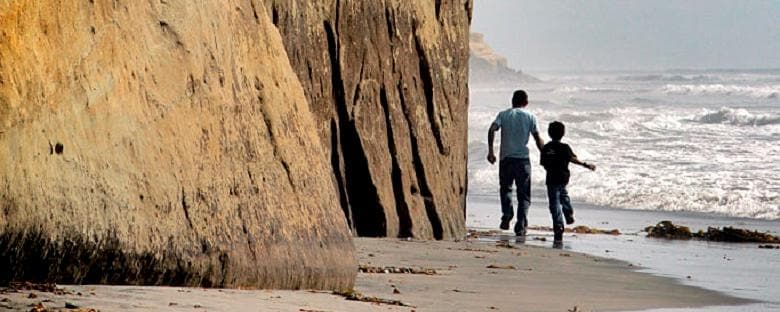 A father and sun running past cliffs in San Diego at Solana Beach.
