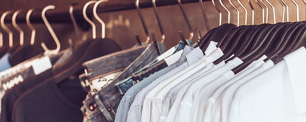A rack of jeans and shirts in a local clothing retail store.