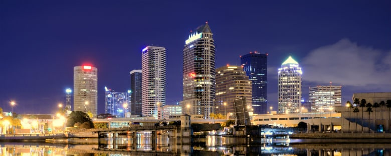 The Tampa skyline lit up at night over the water.