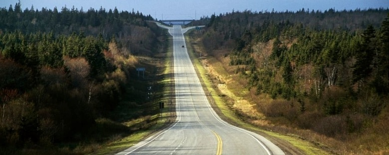 An empty road passes through forests near Vancouver, beckoning adventurers on a road trip