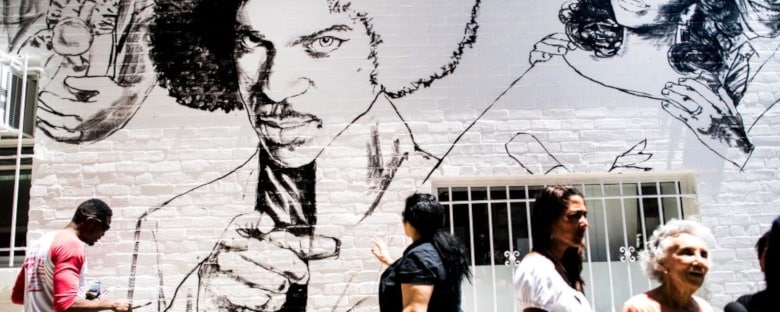 Local artist paints a mural of musician Prince outside Ben's Chili Bowl in Washington, DC