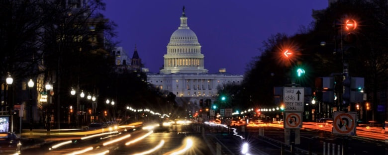 Car headlights streak in the night as they drive through Washington, DC past the US Capitol