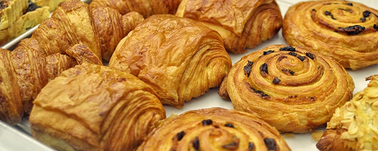 Croissants, pain au chocolate, Danish bread and almond croissant on display in a bakery.