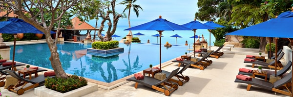Sun loungers and patio umbrellas surrounding a luxurious swimming pool next to the ocean