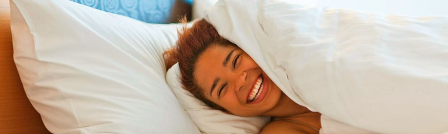 Woman smiling under bed covers