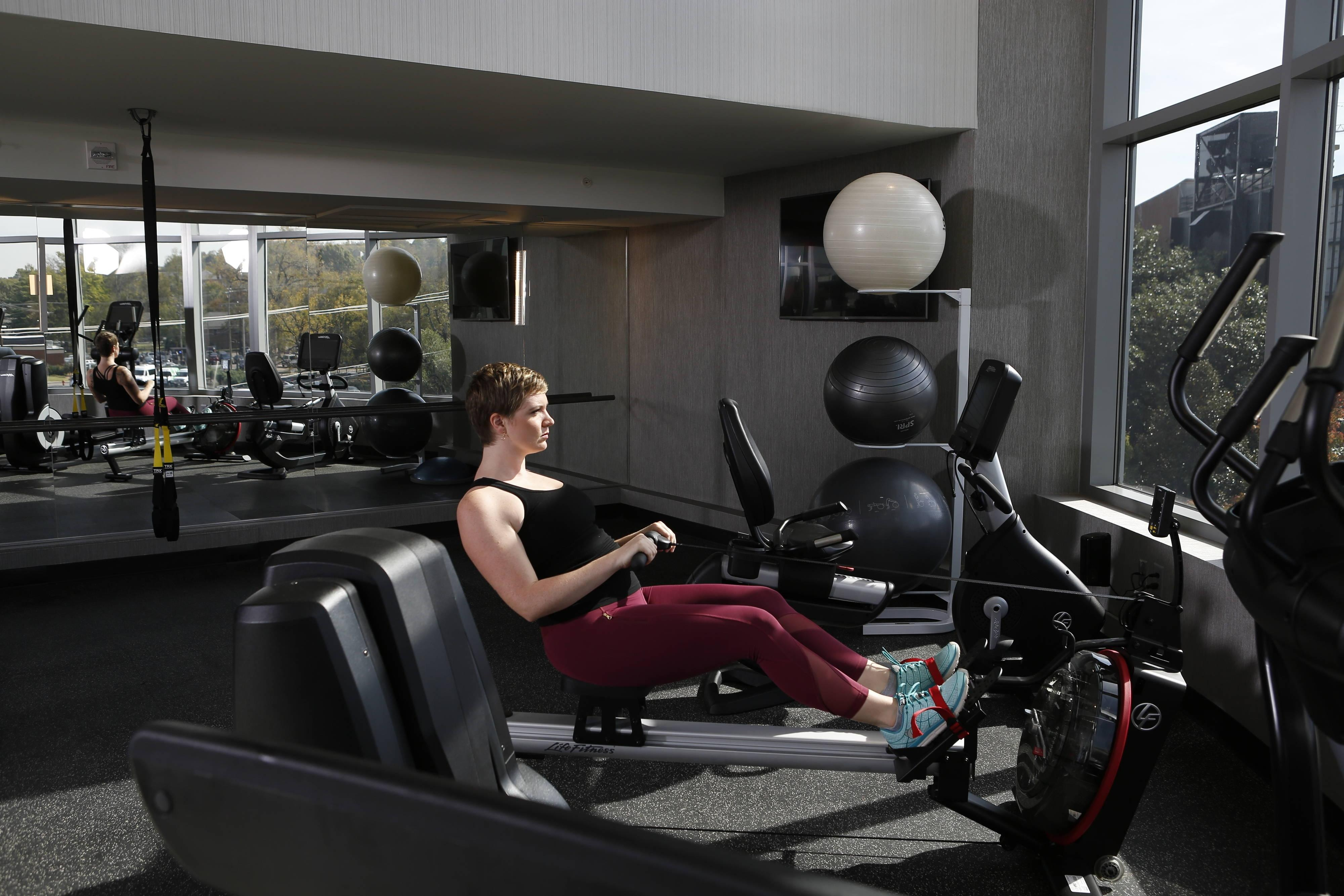 a woman on a row trainer with yoga/stretching area in the background