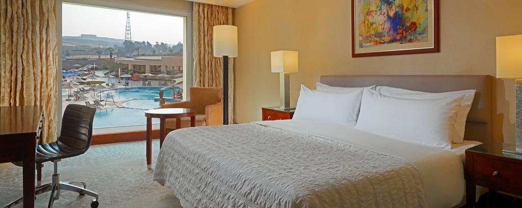 غرفة نزلاء فاخرة تضم سرير كينج بإطلالة على حمام السباحة