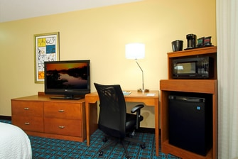 desk and chair in between mini-fridge and microwave and dresser with flat screen tv