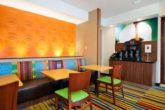 tables and chairs in brightly colored dining room with coffee station