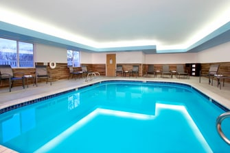 large indoor pool surrounded by patio chairs