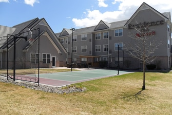 outdoor sport court with tennis net and basketball hoop