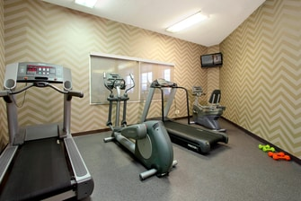 gym with cardio equipment and neon colored free weights