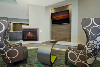 lobby with highback chairs in front of fireplace and flatscreen tv