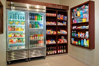 tall glass refrigerator and shelving units stocked with food, drinks, and sundries