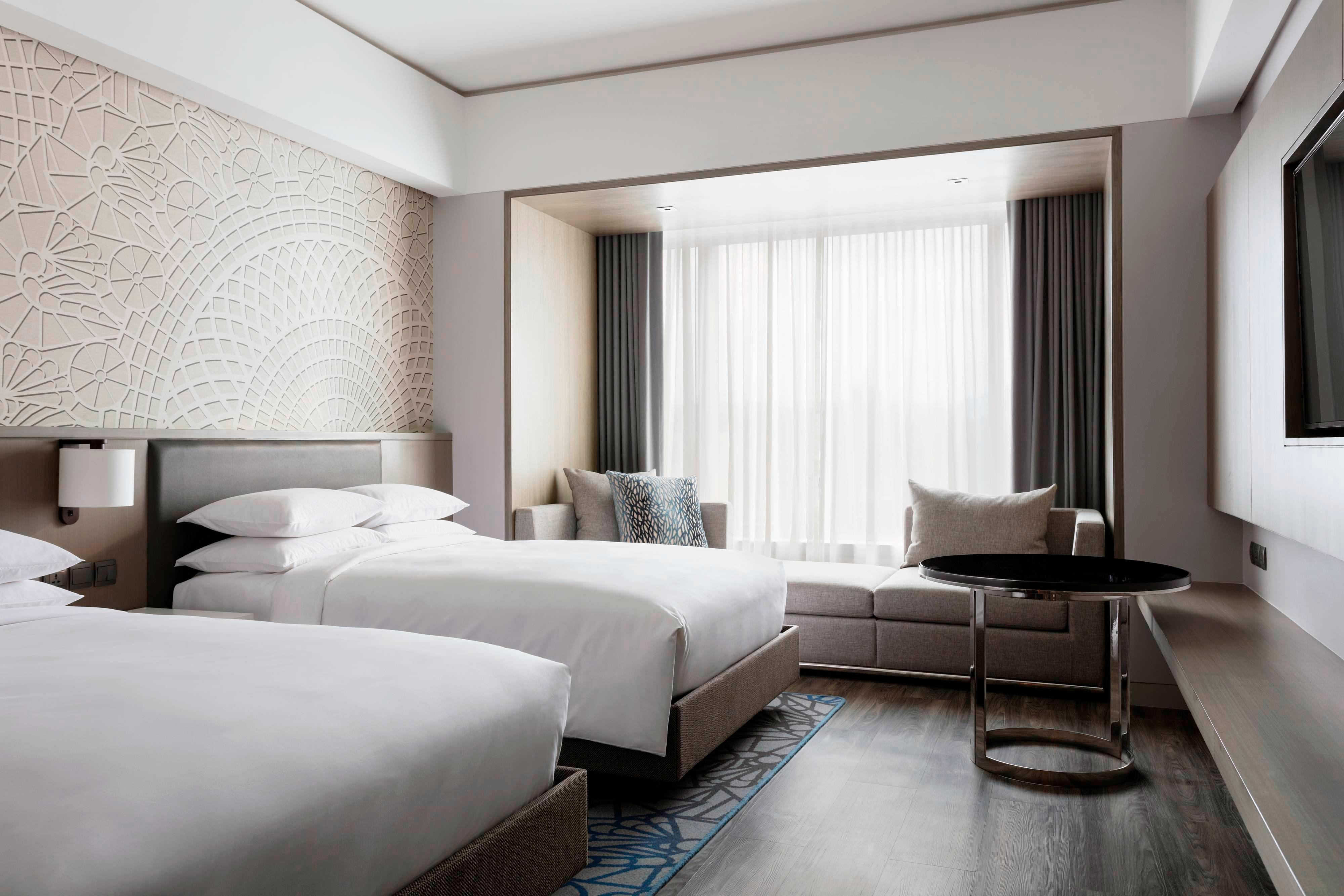 Reserve our twin/twin deluxe guest room for your trip in Clark Freeport Zone, which comes with two twin beds, a sofa, a flat-screen LED television and a table.